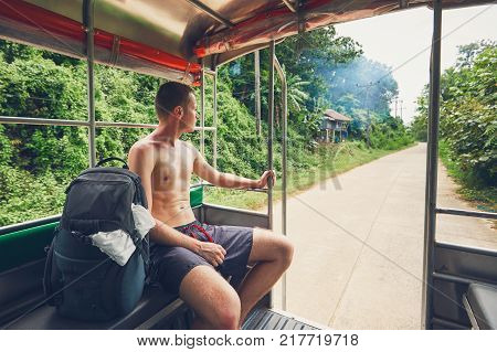 Young man (backpacker) in shorts traveling through Thailand countryside by pick up truck.