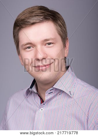 Natural portrait of a young smiling man in shirt. The buttons of the collar undone. Head slightly bent. Neutral grey background