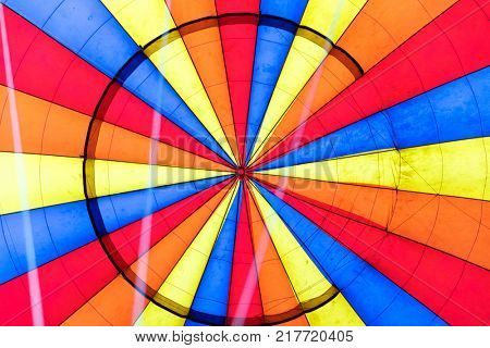 Looking straight up into the inflated canopy of a hot air balloon. Radial abstract background in red, orange, yellow and blue.