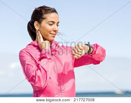 Young woman on beach checking heart rate after run