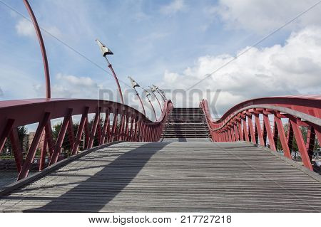 Sinuous wooden stairway with red banister in the blue sky with clouds in the daylight