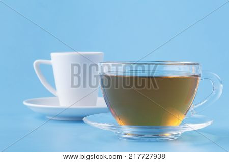 Glass cup with herbal tea on blue background