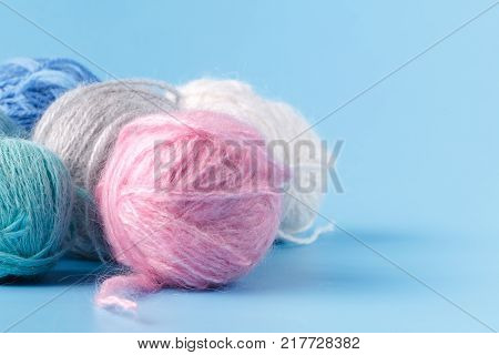 Needlework hobby concept. Wool clews on blue background
