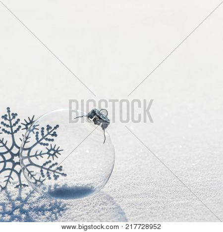 Winter background with decorative transparent glass ball and silver snowflakes shiny on brilliant snow surface. Merry Christmas and Happy New year greeting cards concept