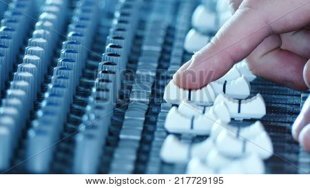 Sound technician hands working on audio mixer faders and knobs. Shallow depth of field. Music production and sound engineering background.