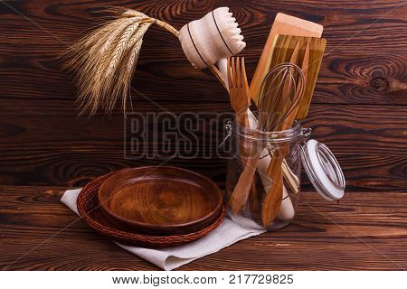 A top view on wooden cutlery spoon, fork, plate, bowl, knife on a dark wooden background. Cutlery for cooking. Close-up of objects.