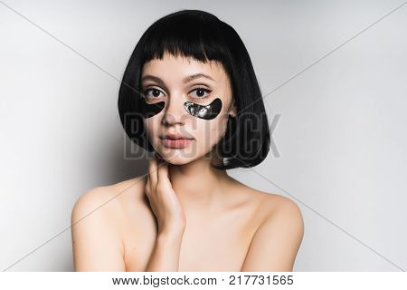 attractive young girl with black hair looks at the camera, under the eyes of cheny silicone patches