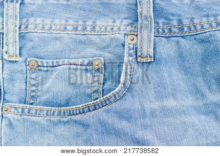 Fragment of the top of the old light blue jeans with waistband two belt loops reinforcing by copper rivets pocket and little pocket