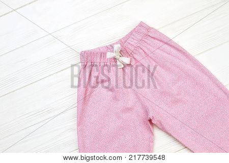 Cute pajama pants on wooden background. Elastic waistband and drawstring for snugly fit. Pink and white.