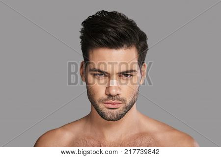 Still irresistible. Handsome young man with adhesive bandage on his nose looking at camera while standing against grey background
