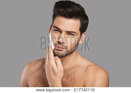 Enjoying morning routine. Handsome young man applying shaving cream and looking at camera while standing against grey background