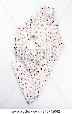 Hand-crafted nightgown for young girl. White long sleeve garment with ruffles and floral print.