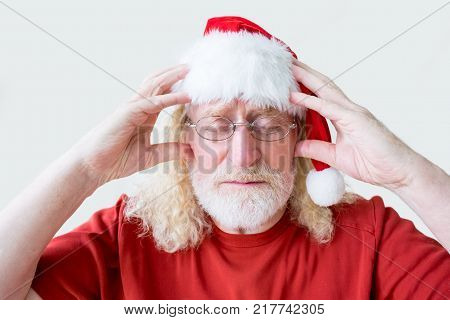 Closeup portrait of tense senior man with closed eye wearing glasses, Christmas hat, keeping hands on head and thinking over problem Christmas or problem solving concept