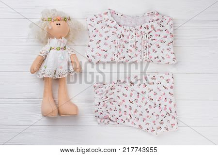 Girls pajama set and doll on wooden background. Floral pattern fabric and cute ruffles. Birthday gift idea.