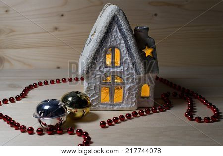 Christmas house candlestick and red christmas chain and two jingle bells/white and silver christmas house candlestick with windows and chimney.