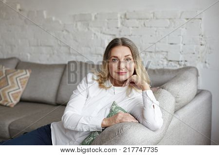 Maturity age womanhood and aging concept. Portrait of charming middle aged grandmother sitting on couch in living room enjoying leisure time looking at camera having pleasant beautiful smile