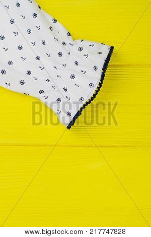Ruffle cuff of girls blouse on yellow background. Nautical pattern and decorative navy edging. Fashionable clothes and beautiful details.
