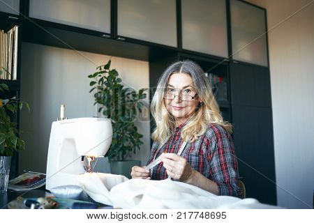 Indoor view of attractive blonde woman pensioner making her living by sewing repairing and altering clothing items working from home sitting in front of sewing machine stitching white fabric