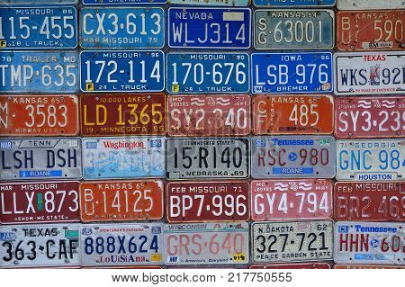 Red Oak Missouri - July 19 2017: Various old American license plates on wall. License plates are from various American states.