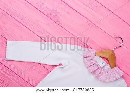 White shirt on wooden hanger. Beautiful garment with pink ruffle collar. Stylish kids clothing background.