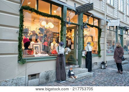 GOTHENBURG, SWEDEN - NOVEMBER 17, 2013: People window shop in Haga, Gothenburg. Haga is a historic residential area, which has become fashionable and popular among tourists.