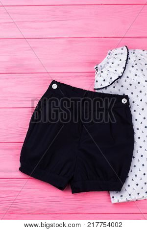 Set of shorts and top on pink wooden background. Nice looking pajama for little girl. Nautical print and ruffles.