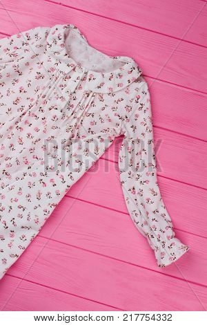 Girls nightie on pink table. Peasant style garment with ruffles and floral pattern. Classic sleepwear for teenagers.