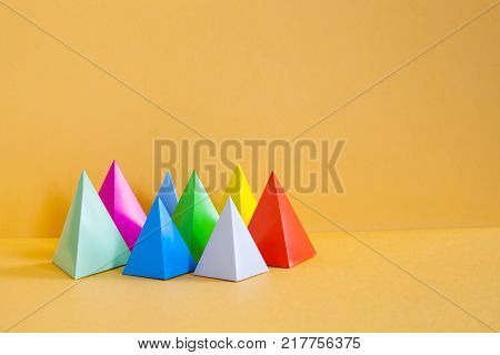 Minimalist design colorful abstract geometrical composition. Three-dimensional prism pyramid rectangular objects, orange background. Gray blue pink red violet green colored solid figures, soft focus.
