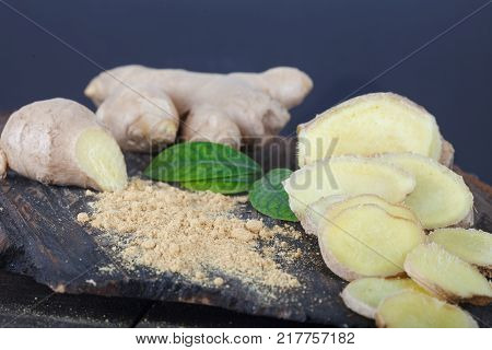 Ground ginger (spice) and fresh ginger root on a wooden board