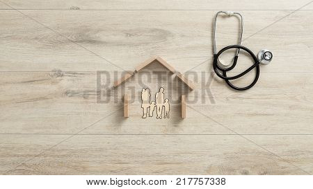 Cut outs of a family with children in a house with a stethoscope lying on a wooden table alongside conceptual of home insurance.