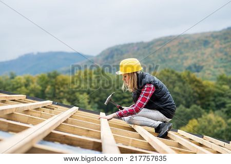 Female worker on the building site. Young woman working as a roofer. House construction.