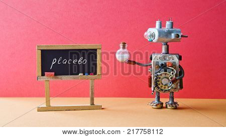 Placebo effect concept Medic robot drugs tube, black chalkboard with handwritten word placebo. Pink wall brown floor background