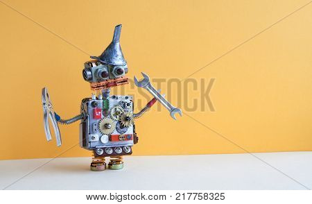 Friendly robot serviceman pliers handwrench. Fixing maintenance concept. Creative design toy with metal funnel hopper, cogs wheels gears silver metallic body. Yellow wall, beige floor background. Copy space photography.