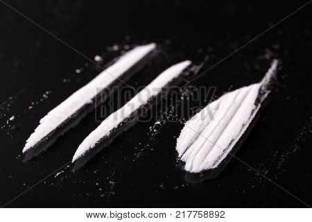 Two lines and pile of cocaine on black background, closeup