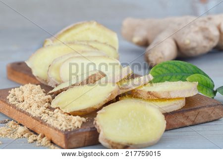 Ginger root - Fresh ginger root and sliced on wooden board