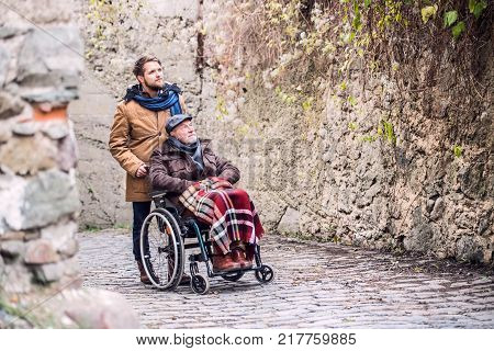 Father in wheelchair and young son on a walk in old town. A carer assisting disabled senior man.