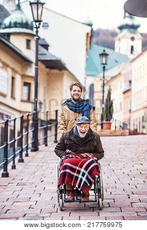 Father in wheelchair and young son on a walk, laughing. A carer assisting disabled senior man.