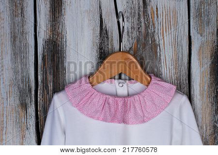Pink ruffle collar of pajama. White cotton top on wooden hanger. Stylish sleepwear for little lady.