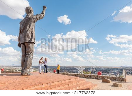 BLOEMFONTEIN SOUTH AFRICA DECEMBER 11 2016: Unidentified visitors at the 6.5m bronze statue of Nelson Mandela on Naval hill in Bloemfontein