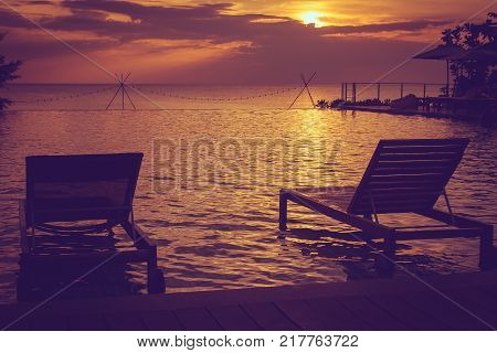 Silhouette daybed on swimming pool with beautiful seascape view and sunset in the background. (Selective focus)
