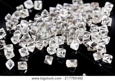 Collection of faceted natural transparent diamonds in macro on a black background