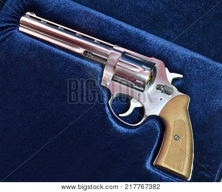 Revolver magnum 357 handgun on blue velvet background