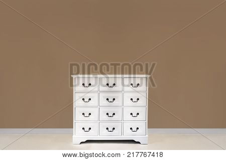 The white color dresser with many drawers is on the floor in the bedroom.