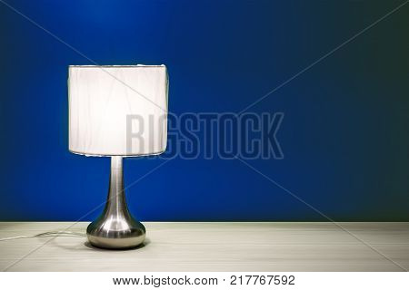 Lamp night light in a dark background. Minimal concept. Night lamp with round shade standing on a wooden table on a background of blue walls to read burns brightly in the dark.