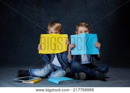 The studio shot of children with books and tablet