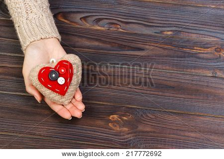 Woman's hands with beautiful accurate knitted red heart. White cozy knitted sweater on wooden background. Concept of giving help. Love concept with copyspace.