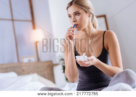 Powerful painkiller. Beautiful young woman sitting on the bed and putting a blue capsule into her mouth while holding a pill organizer
