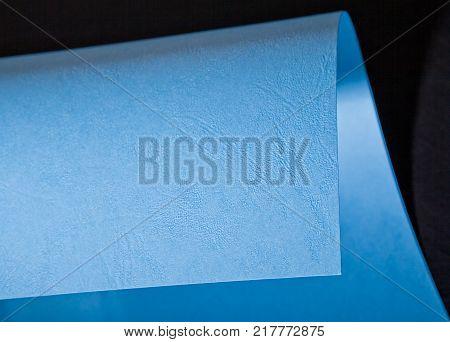 Curled corner of blue paper. Mock up. Close up. Macro shot