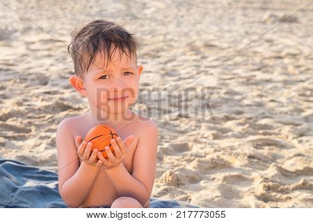 A boy is sitting on the beach with a small ball in his hands. Summer vacation on the beach