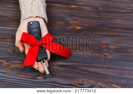 Car key with red bow in woomen hand on wooden background. Valentine's Day concept.